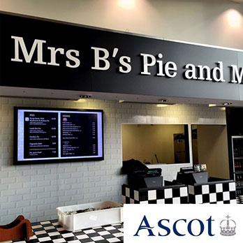 Mrs B's Pie and Mash restaurant at Ascot Racecourse with a digital signage menu board on the wall behind the counter