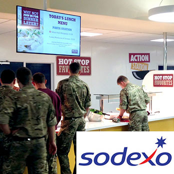 Soldiers in Colchester Garrison army barracks queuing at Hot Stop restaurant station with digital signage menu boards hanging from the ceiling