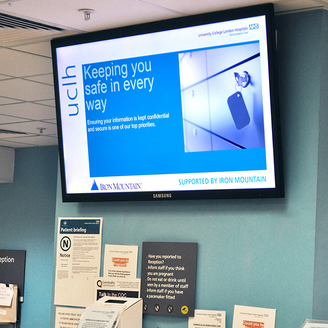 Healthcare digital signage screen in University College Hospital London displaying a message about keeping information safe