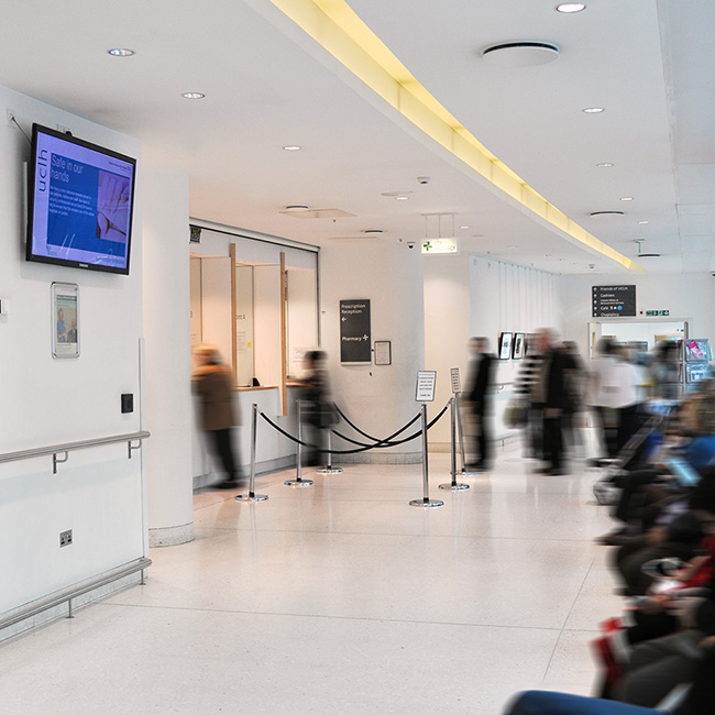 Busy scene of patients waiting in a corridor at University College Hospital in London, watching a healthcare digital signage screen