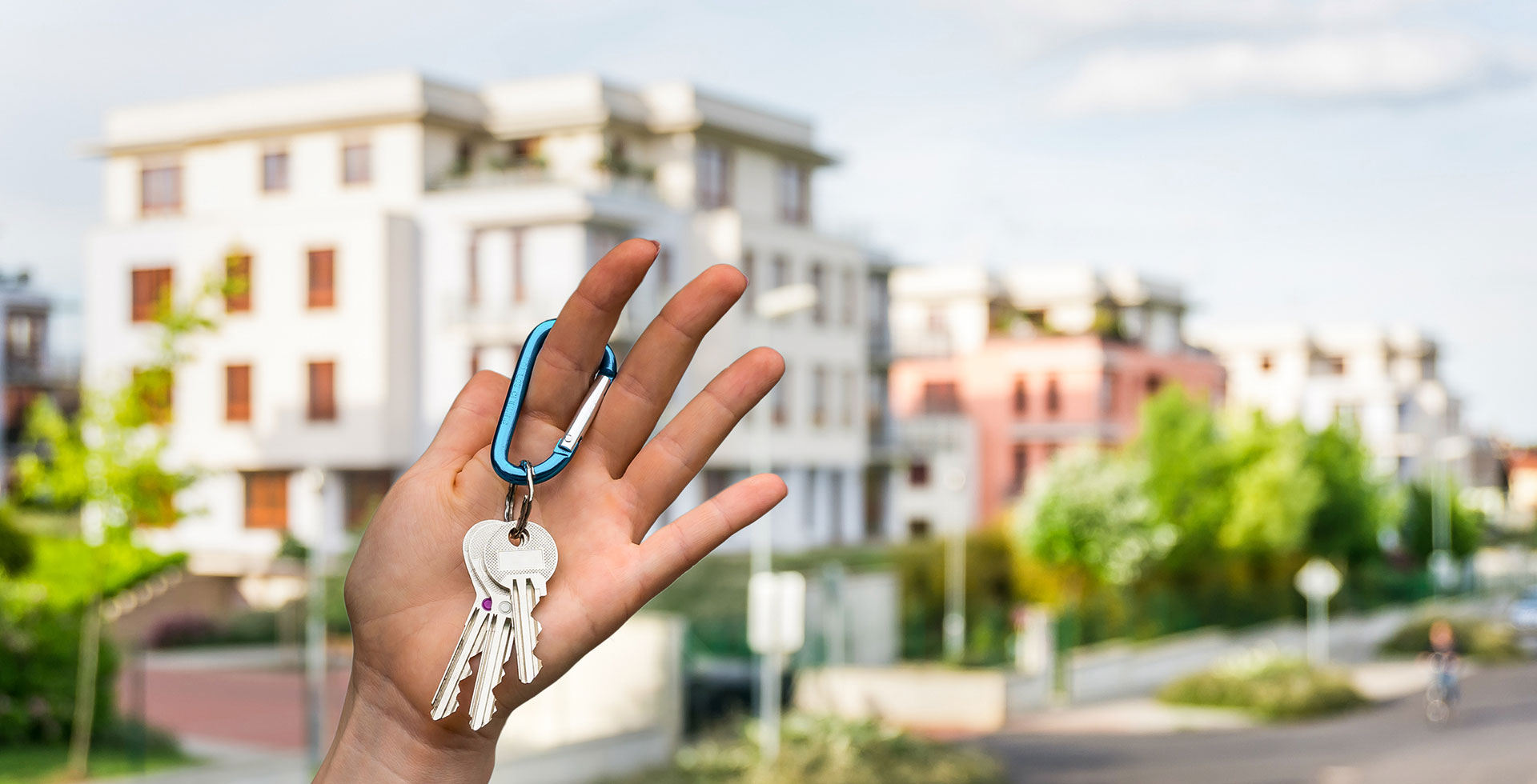 A hand holding house keys with blurry apartment buildings in the background
