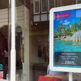 Travelbag digital signage screen kiosk in window of store showing Indian Ocean Seychelles Promotion