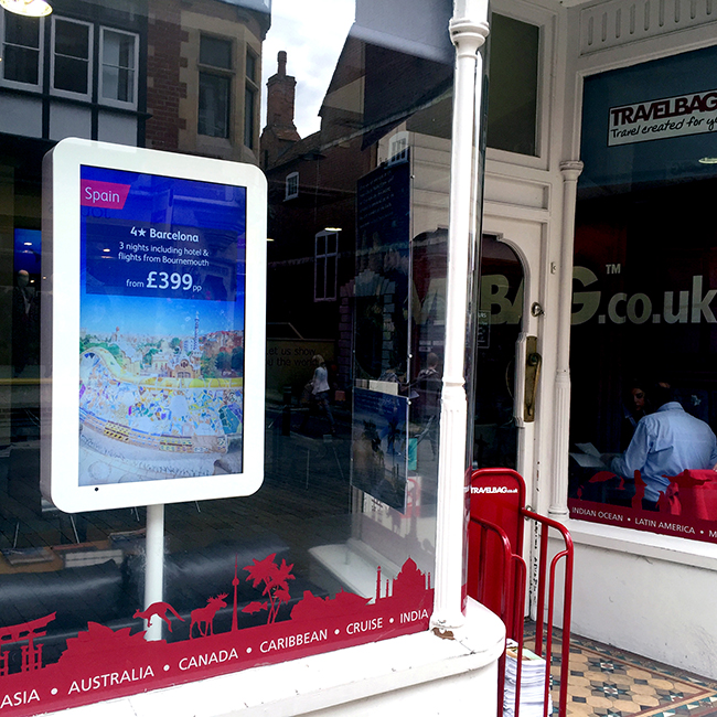 Digital signage screen in a kiosk in a Travelbag UK shop window, displaying advertising for Barcelona vacations