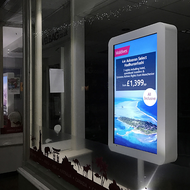 Digital signage screen in a kiosk in a Travelbag UK shop window, displaying advertising for Maldives vacations
