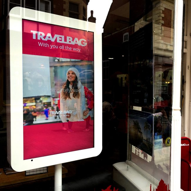 Digital signage screen in a kiosk in a Travelbag UK shop window