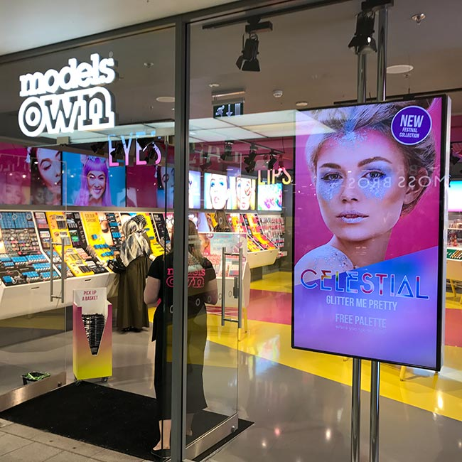 Digital signage portrait screen in window of Models Own store advertising Celestial Glitter Me Pretty Free Makeup Palette